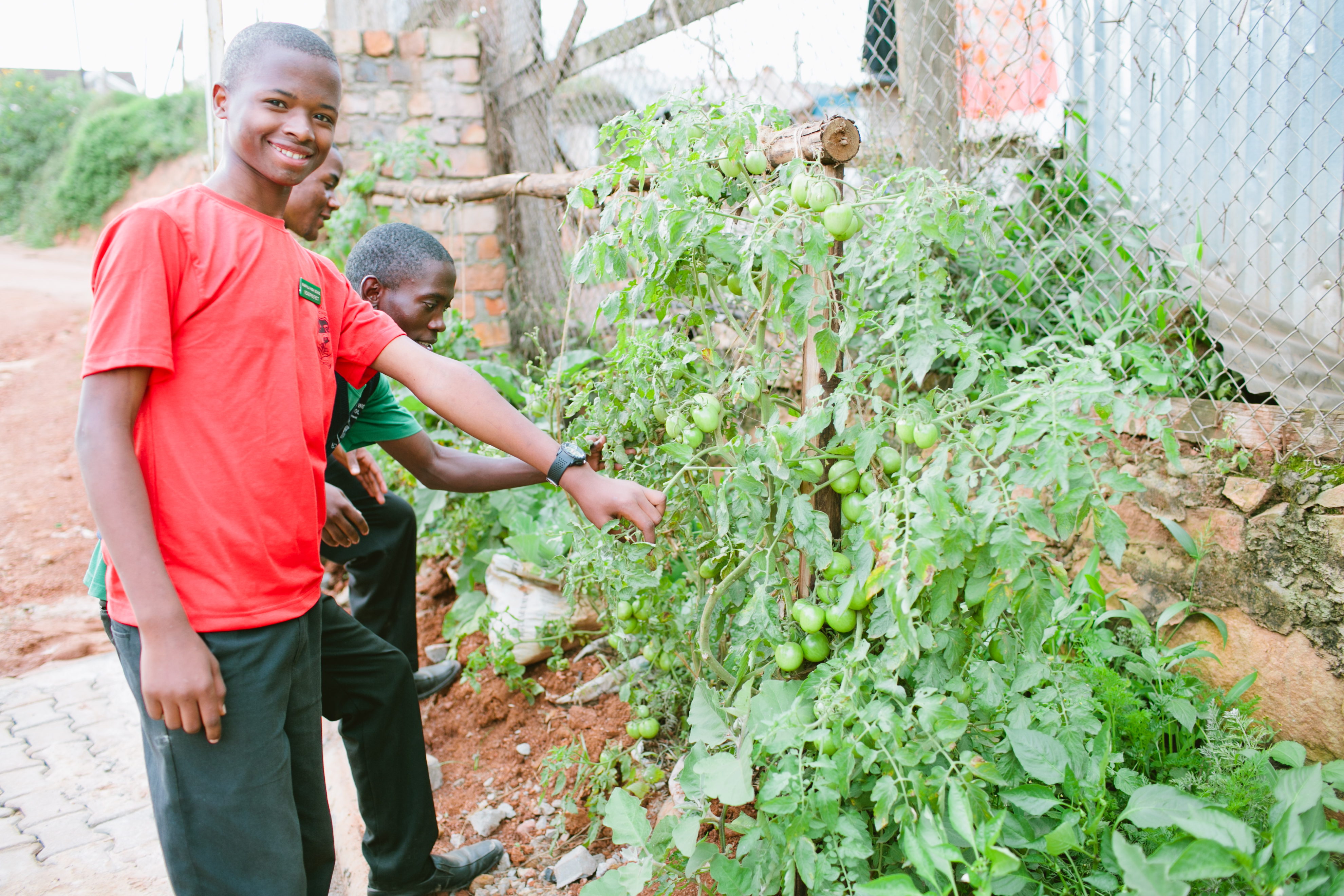 Student at Kampala High School shows Student Business Club garden project . Photo by Ashley Turner for Educate!