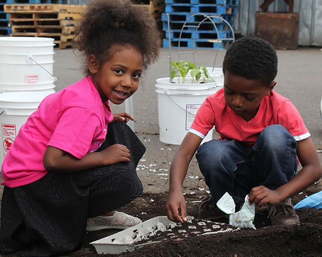 Nylinn and Raili plant seeds at Marion-Polk Food Share. Image courtesy of Marion-Polk Food Share. Used with permission.