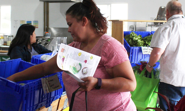 Farm Share Rx Distribution – A Farm Share Rx participant selects fresh vegetables for her weekly share.