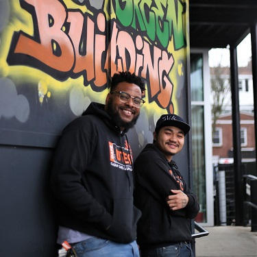 A UTEC staff mentor with a young adult, both smiling as they lean against the outer wall of UTEC's main program building.